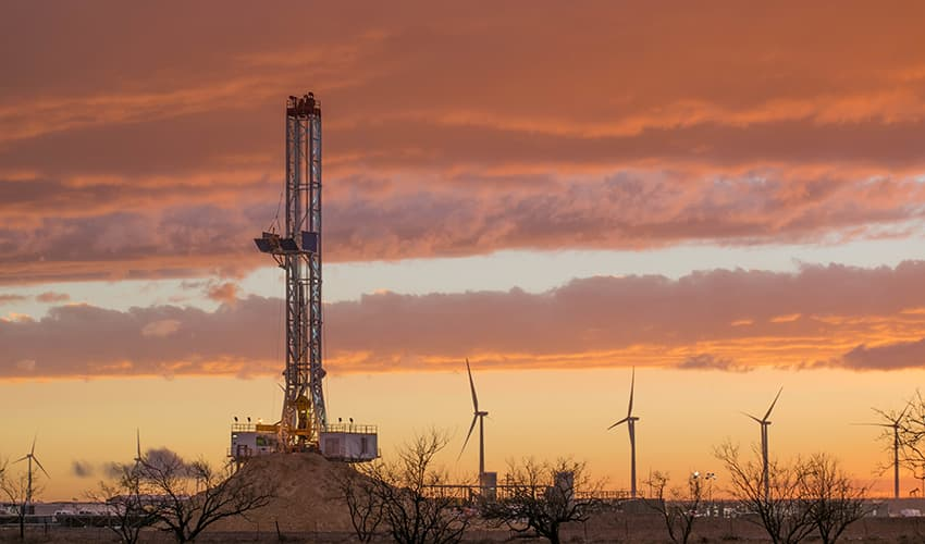 A fracking operation with wind turbines in the background.