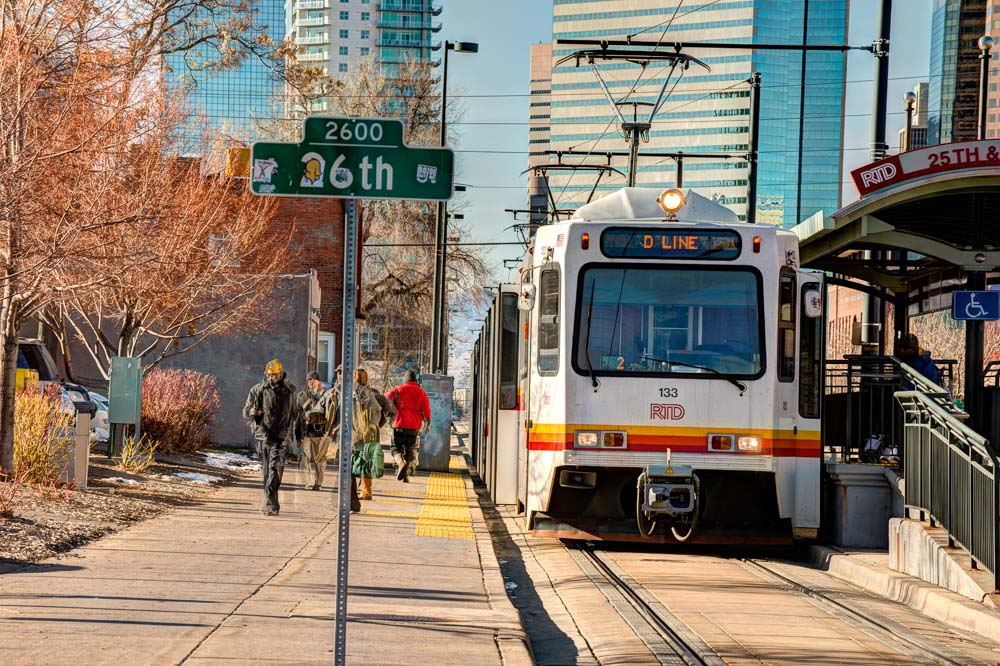 A light rail train waits at a station in Denver