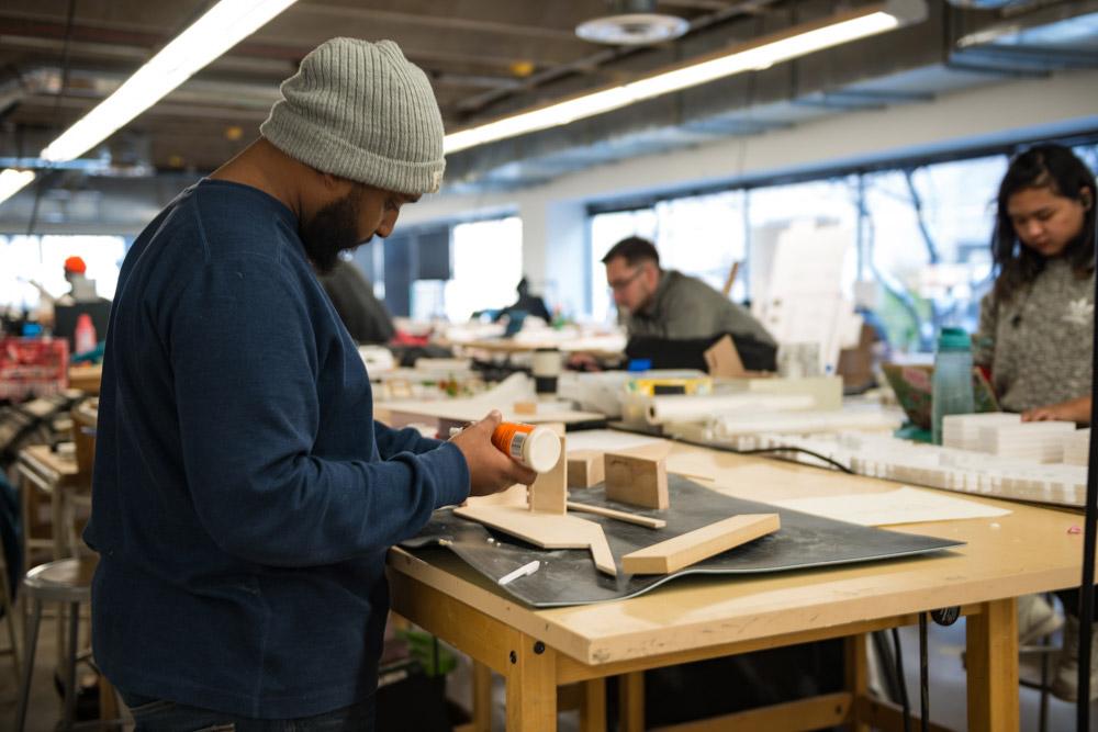 A male undergraduate student glues a model in studio