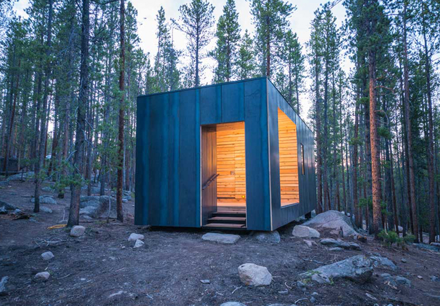 A steel clad cabin in a pine forest at dusk