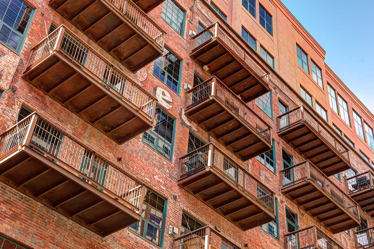 Exterior of historic brick building with rows of balconies