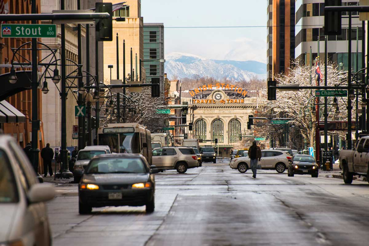 City street with Union Station and mountains in background