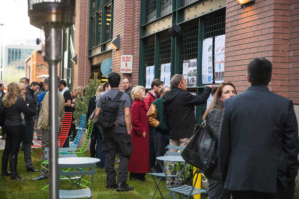 Many people mingling in an alley looking at student projects