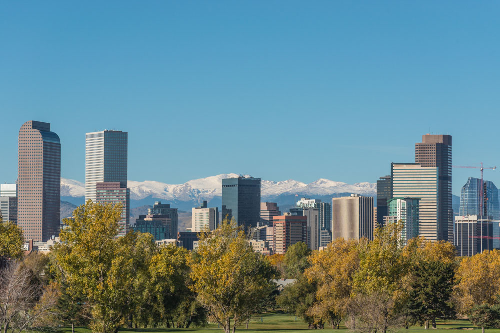 Denver skyline against snowcapped montains and a blue sky