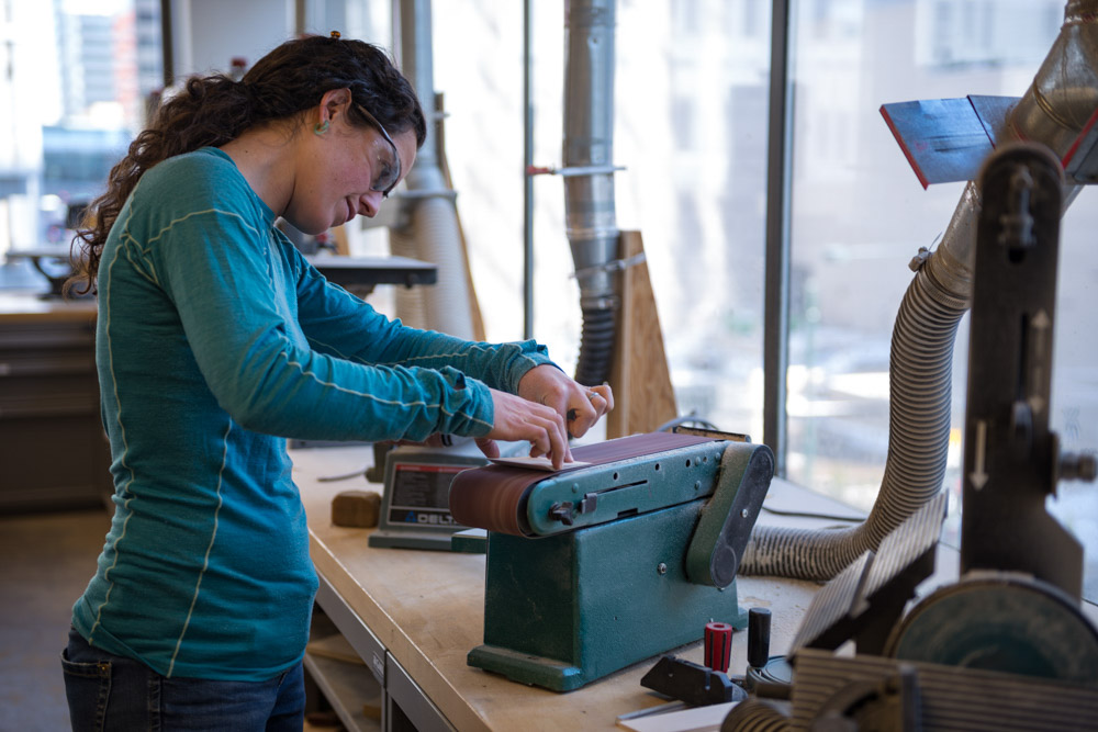 a female student uses a sanding tool in the fabrication lab