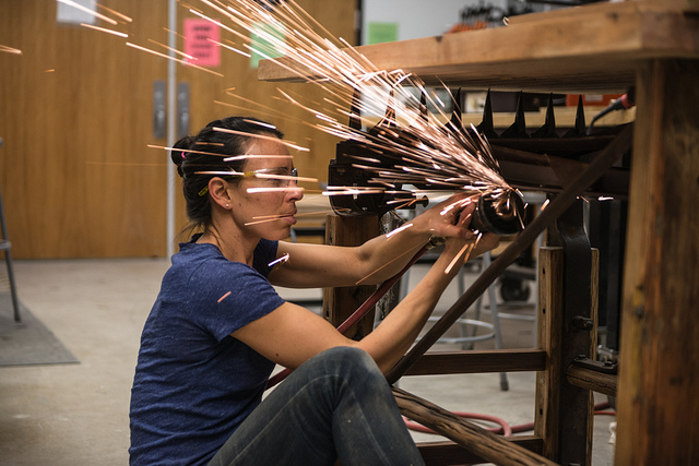 A woman grinds metal as sparks fly