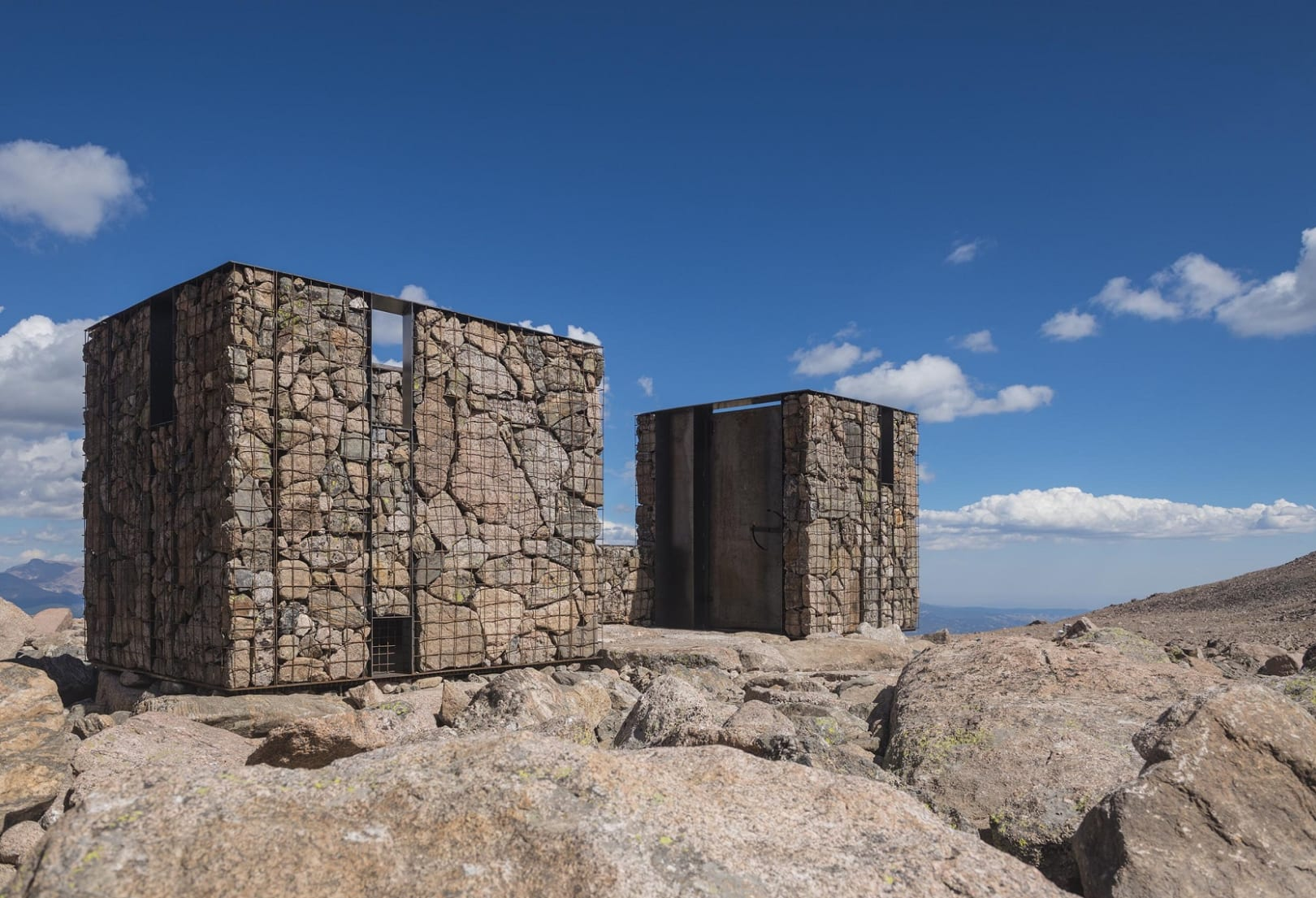 2 cube buildings constructed with rocks on a mountain